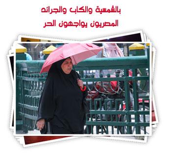 بالشمسية والكاب والجرائد.. المصريون يواجهون الحر