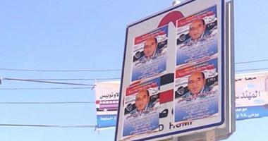 مرشح بأسيوط يطمس إشارات مرور الطريق السريع بملصقات دعايته الانتخابية