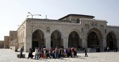مستوطن يكتب شعارات يهودية على أحد أبواب المسجد الأقصى