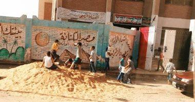 طلاب مدرسة الشيماء بالسويس يحملون الرمال