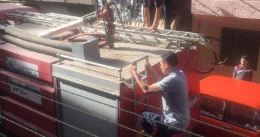 """بالصور.. رجال الحماية المدنية ينقذون قطة سقطت فى """"منور"""" بشبرا الخيمة"""