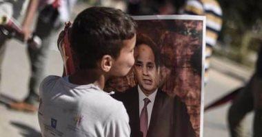 بالصور.. طفل فلسطينى فى شوارع غزة يقبل صورة الرئيس عبد الفتاح السيسي