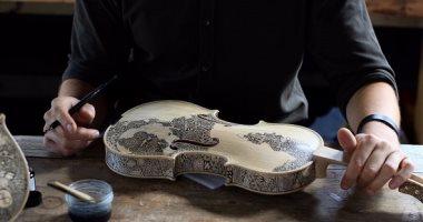 """الوتر يقدر يقول حكايات.. فنان يرسم على """"الكمان"""" للربط بين الموسيقى والقراءة"""