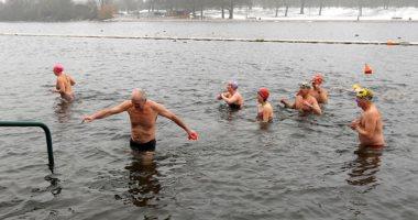 صور.. بريطانيون يتحدون الثلوج بالسباحة فى بحيرة سربنتين بلندن