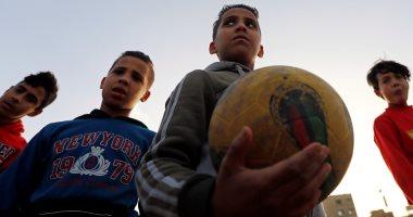 كرة القدم فى القلب.. أطفال يستغلون ساحات بجوار المقابر للعب .. صور