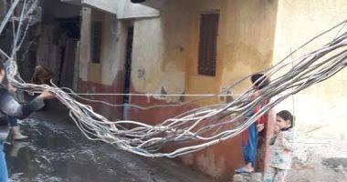 صور.. أهالى قرية أبيس بالإسكندرية يستغيثون من كابلات الكهرباء بالشوارع