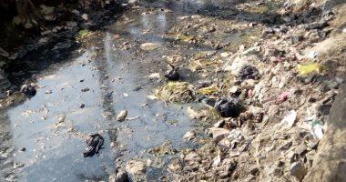 قارئ يرصد تغطية القمامة لترعة رئيسية بقرية فى العياط