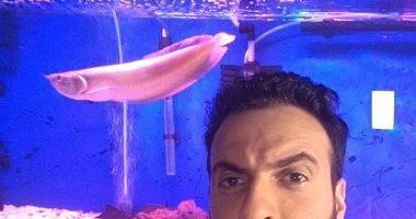 """أنا وأليفى.. """"جهاد """" يشارك بصورة مع سمكه: """"أعش هواية تربية أسماك الزينة"""""""