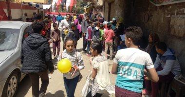 صور.. مواطنون يحتفلون مع الأطفال بالبلالين أمام اللجان فى عين شمس