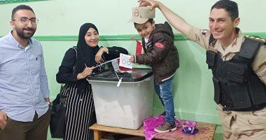 زوجة الشهيد محمود منير تصطحب طفلها بزى عليه صورة والده للاستفتاء بالشرقية