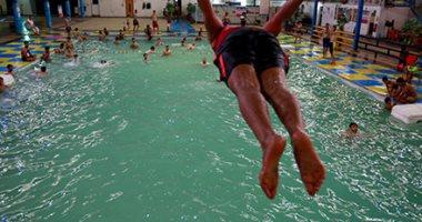 صور.. مواطنون بالعراق يهربون من حرارة الجو إلى الأحواض والأنهار