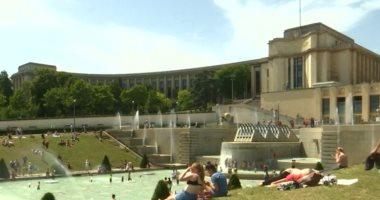 """شاهد.. سياح يلجأون إلى """"نوافير المياه"""" لمواجهة ارتفاع الحرارة فى باريس"""
