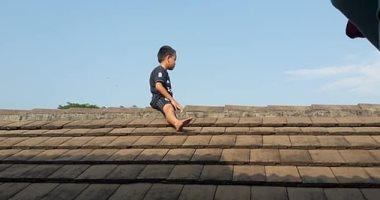 """""""عيال عفاريت"""".. طفل إندونيسى يتسلق سطح عيادة هرباً من الختان.. اعرف حكايته"""