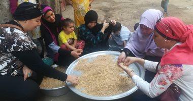 صور .. عضوات القومى للمرأة ينظفن القمح خلال حملة طرق الأبواب ببنى سويف