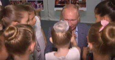 شاهد.. الرئيس الروسى بوتين يجلس على ركبتيه ليقبل يد طفلة صغيرة