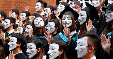 طلاب بأقنعة يهتفون بشعارات المحتجين فى حفل تخرجهم بهونج كونج