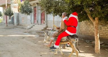 """صور.. بابا نويل يوزع هدايا للأهالى والأطفال المرضى """"على حمار"""" بإحدى قرى أسيوط"""