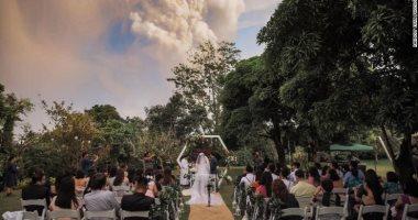 فوتو سيشن مجنون.. عروسان يلتقطان صور زفافهما أثناء ثوران بركان فى الفلبين