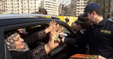 الشرطة توزع الهدايا والورود والشيكولاتة على المواطنين في التحرير.. صور