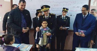 رجال الشرطة يوزعون كراسات رسم وكتيبات على طلاب المدارس بالمحلة ..صور