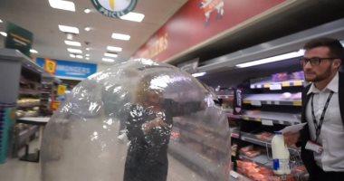 """هستيريا كورونا.. سيدة تتسوق """"داخل كرة بلاستيك"""" خوفا من العدوى ببريطانيا.. فيديو"""