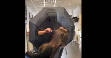 للوقاية من وباء كورونا.. هولندية تحتمى بمظلة لتصفيف شعر الزبائن