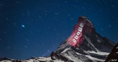 """من وسط العتمة نور.. فنان يتحدى كورونا بـ""""رسائل الأمل"""" على قمة جبل بسويسرا"""