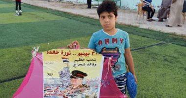 أطفال دماص بالدقهلية يحتفلون بـ30 يونيو بطائرات ورقية تحمل صور الشهداء