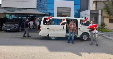 عمال الورديات بالعاشر من رمضان يتوجهون للجان الانتخابية بالأعلام.. صور