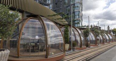 مطعم بريطانى يقدم الطلبات تحت مظلات زجاجية منفصلة خوفا من كورونا.. صور