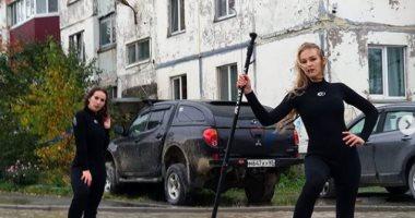 فتيات يلفتن الأنظار لمشكلة تجمع المياه فى شارع مدينة روسية بطريقة مميزة.. صور