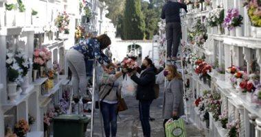 مواطنو إسبانيا يزينون المقابر بالورود احتفالاً بيوم القديسين.. ألبوم صور