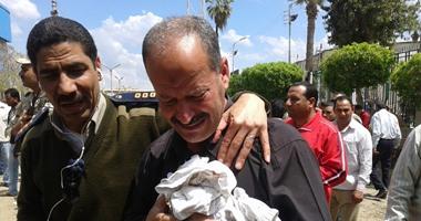 والد أحد الضحايا يحمل ملابس نجله