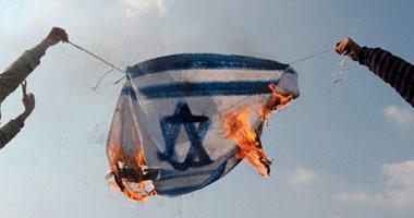 شاب ينتزع العلم الإسرائيلى من أعلى مبنى السفارة العبرية ويحرقه S120091014133