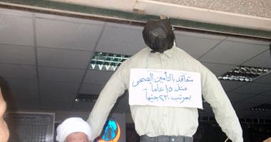 """لافتة على التمثال المعلق """"متعاقد بالتأمين الصحى منذ 15 عاما بمرتب 230 جنيها"""""""