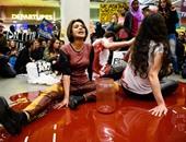 """بالصور..نشطاء إنجليز يجلسون فى """"بركة دم """" اعتراضا على منع دخول اللاجئين"""