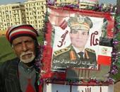 """رجل مسن يزين صورة الرئيس السيسى ويرفعها بـ""""التحرير"""" احتفالا برأس السنة"""