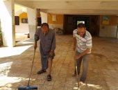 مدير مدرسة وعدد من المدرسين ينظفون آثار السيول فى أسيوط