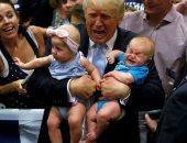 بالصور.. على طريقة فيلم طيور الظلام.. ترامب يكسب ود الناخبين بحمل الأطفال