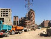 بالصور.. انتشار ظاهرة البناء أسفل أبراج الكهرباء بأسيوط