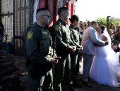 صور.. حفل زفاف على الحدود الأمريكية المكسيكية خلال فتح بوابة بالجدار العازل