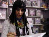 فنانة تشكيلية ترتدى ملابس كليوباترا وتقدم لوحاتها فى معرض الكتاب