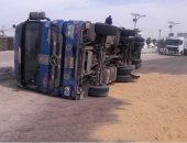إصابة سائق بسبب انقلاب سيارة نقل أعلى الطريق بمدينة الشيخ زايد