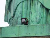 صور.. بعد ساعات من التفاوض.. شرطة نيويورك تعتقل امرأة تظاهرت فوق تمثال الحرية
