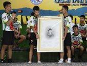 أطفال كهف تايلاند يحملون صورة الغطاس المتوفى أثناء محاولة إنقاذهم بمؤتمر صحفى