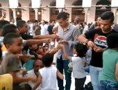 شباب يوزعون البلالين والفشار على الأطفال بساحة الأزهر احتفالا بالعيد