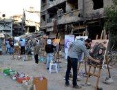 صور.. فنانون سوريون يرسمون لوحات لمعاناة شعبهم فى شوارع دمشق وسط الدمار