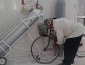 مواطن برسل صورة عامل بمستشفى منفلوط ينفخ دراجته الهوائية من أنبوب الأكسجين