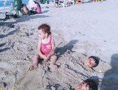 صور.. الأطفال يشكلون لوحات فنية بأجسادهم فى رمال مصيف بلطيم