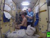 """شاهد.. رائد فضاء يستخدم """"موس"""" و """"مكنسة كهربائية"""" لقص شعر زميله"""